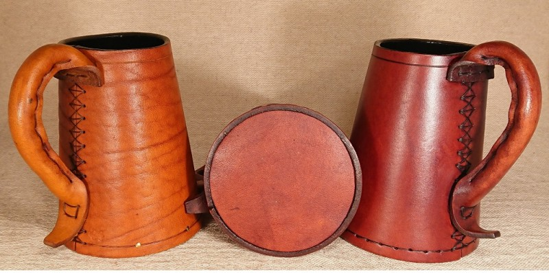 Leather tankards look intriguing and have been used since the medieval period.  A picture of two brown full grain leather tankards.